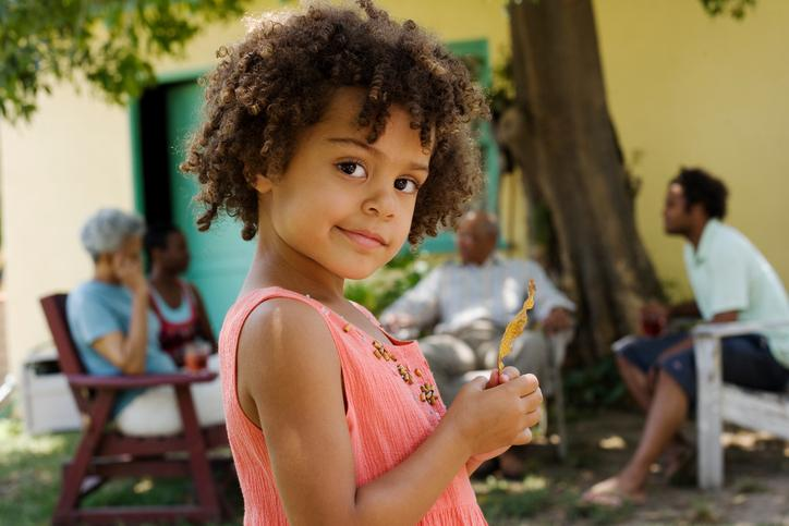 Girl standing outdoors smiling with people in background